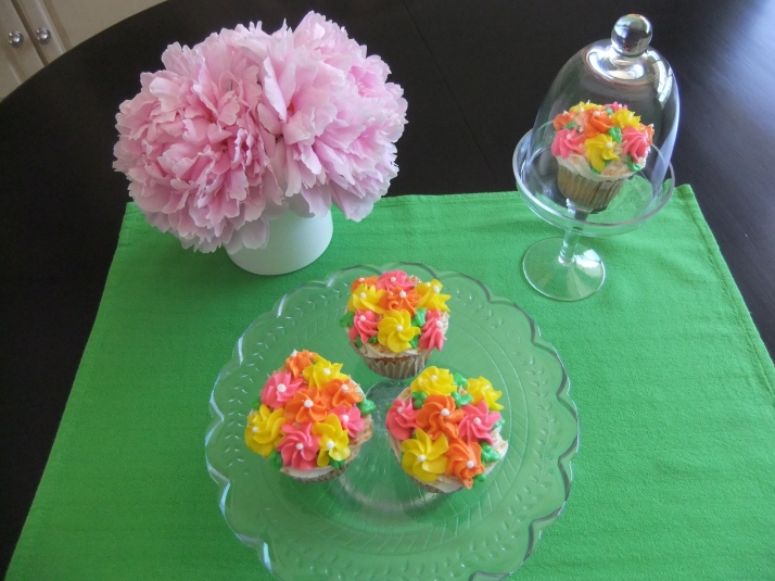 Lime Cupcakes with a Lime Curd Whipped Filling.  Vanilla Frosting with Toasted Coconut edges and decorated with colorful delicate flowers.